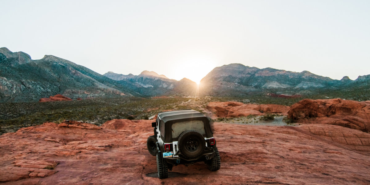 A Jeep straddles a slickrock hill