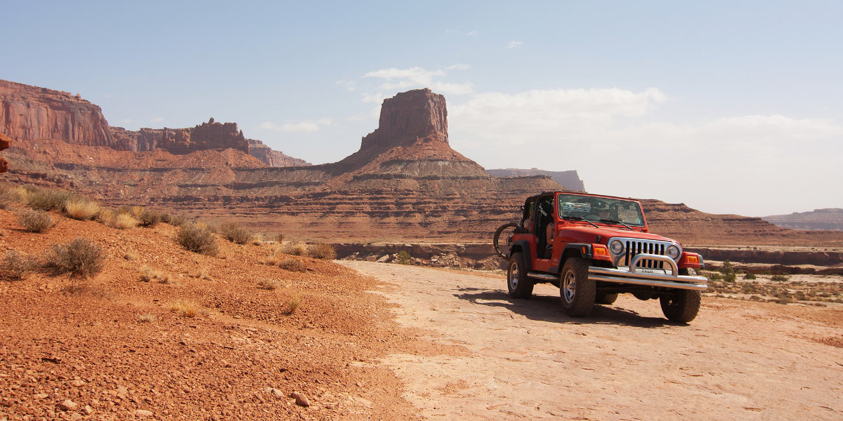 A Jeep on the White Rim Road with towering sandstone cliffs in the background