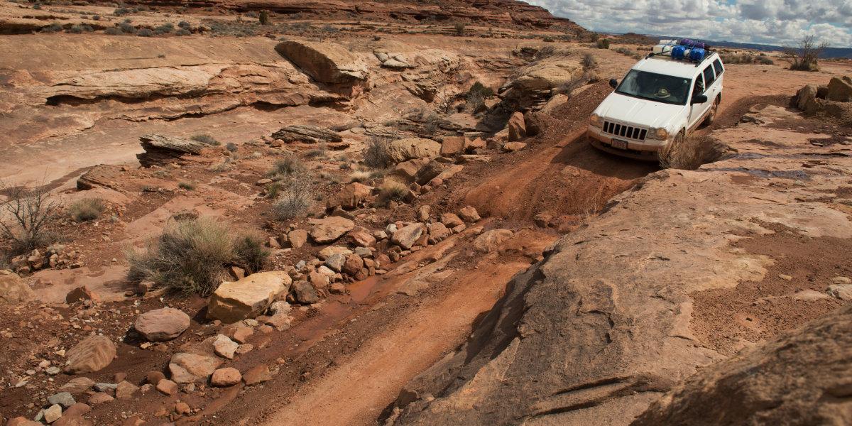 A Jeep navigates rough terrain on the White Rim Road