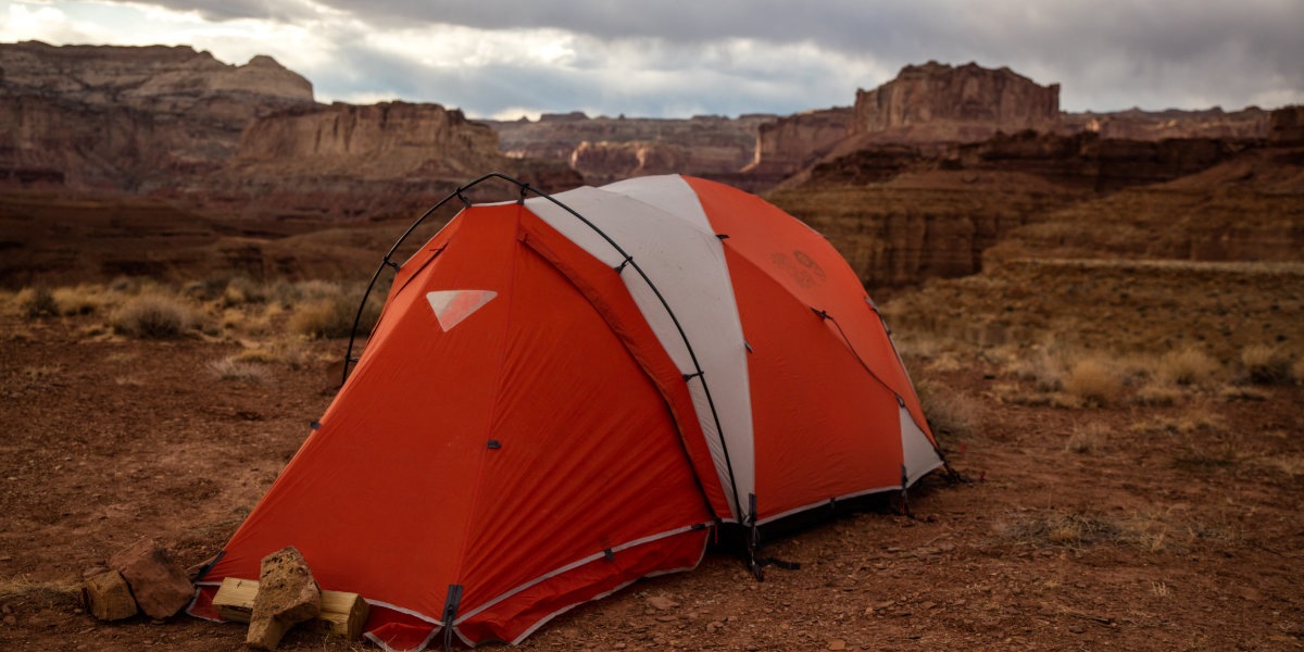 An orange tent with dramatic views of red cliffs in the background