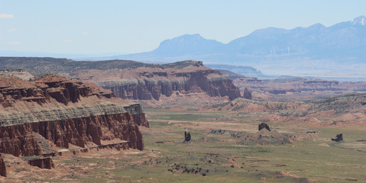 A large open desert area flanked by red cliffs