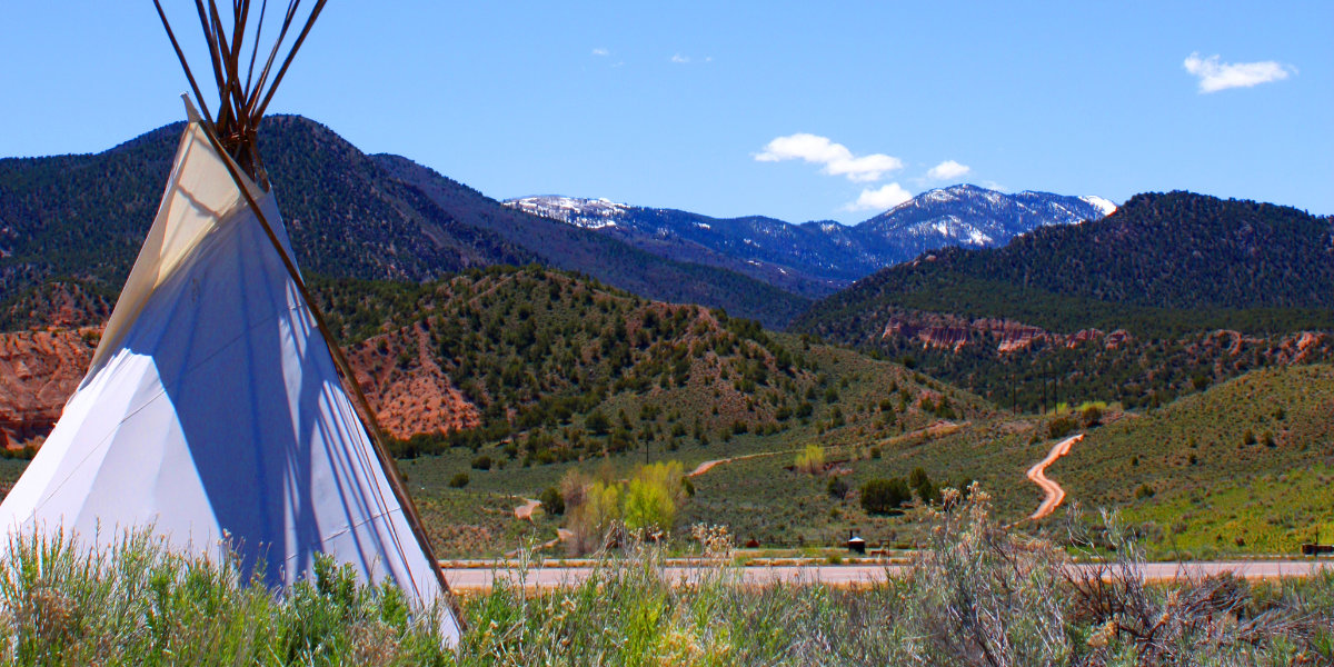 A tipi in the foreground and a view of I-70 in the background