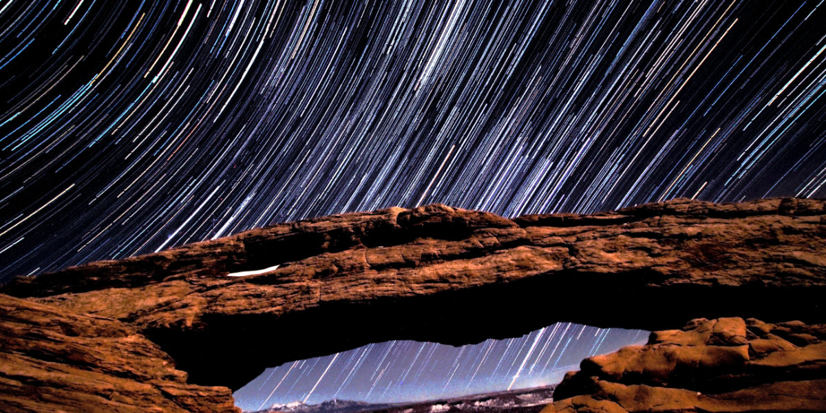 A time lapse photograph of the night sky above an arch