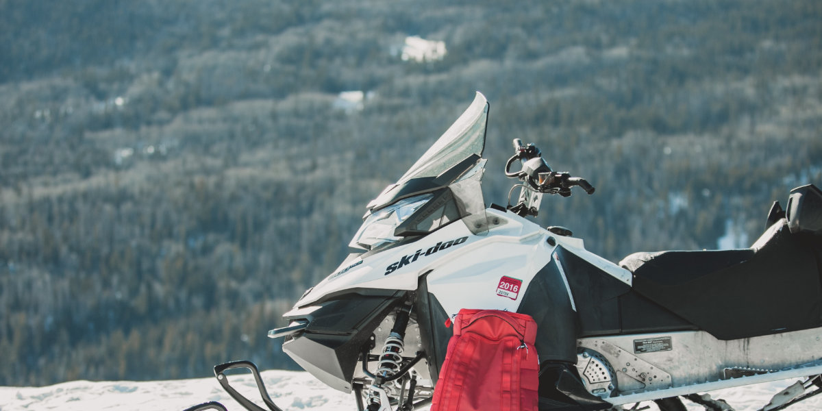 A snowmobile parked at the summit with a great alpine view