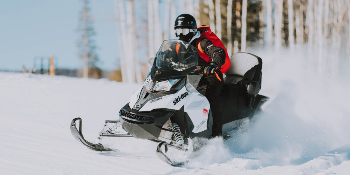 A man rides a snowmobile with aspen trees in the background