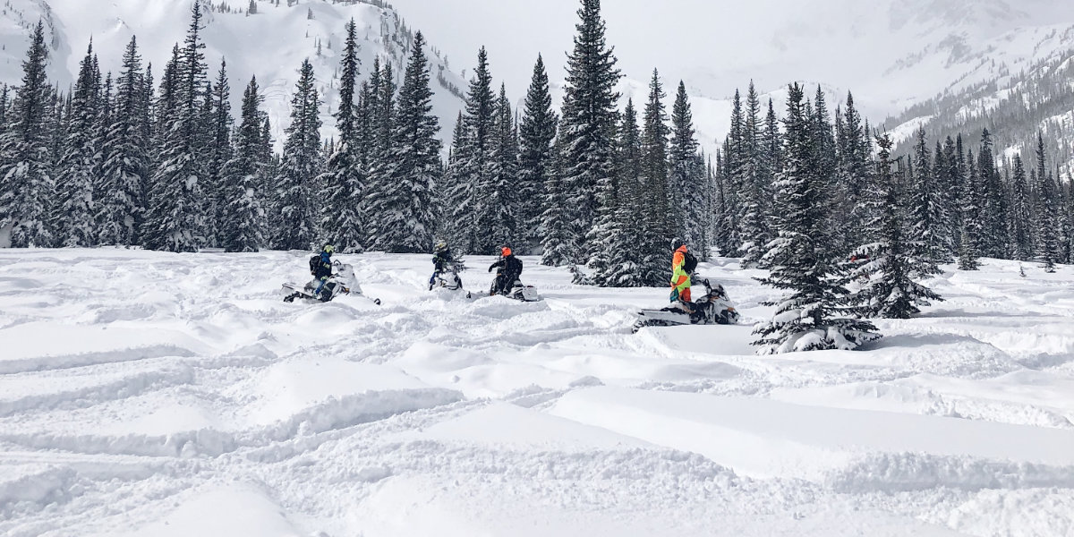 A group of people snowmobiling in a play-area