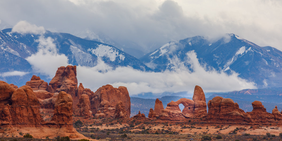 Red rock arches with snowy mountain backdrop