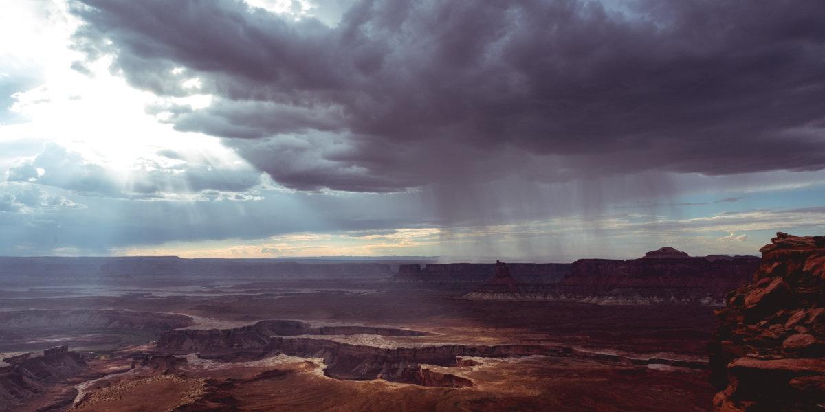 A rain storm seen from a distance over a muted desert