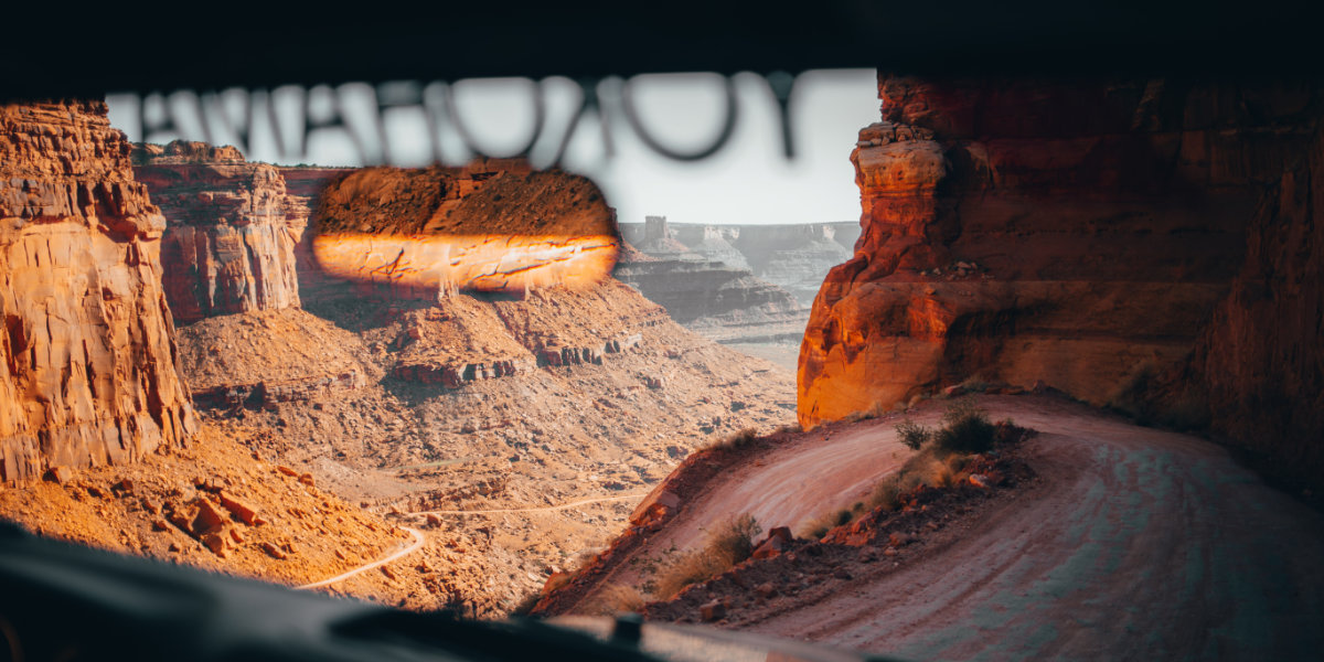 The view from inside a vehicle that is driving on a scenic, winding dirt road