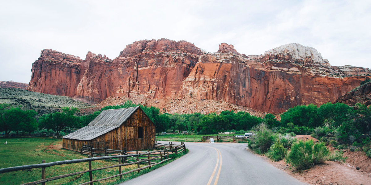 A barn and field  set against a red cliff