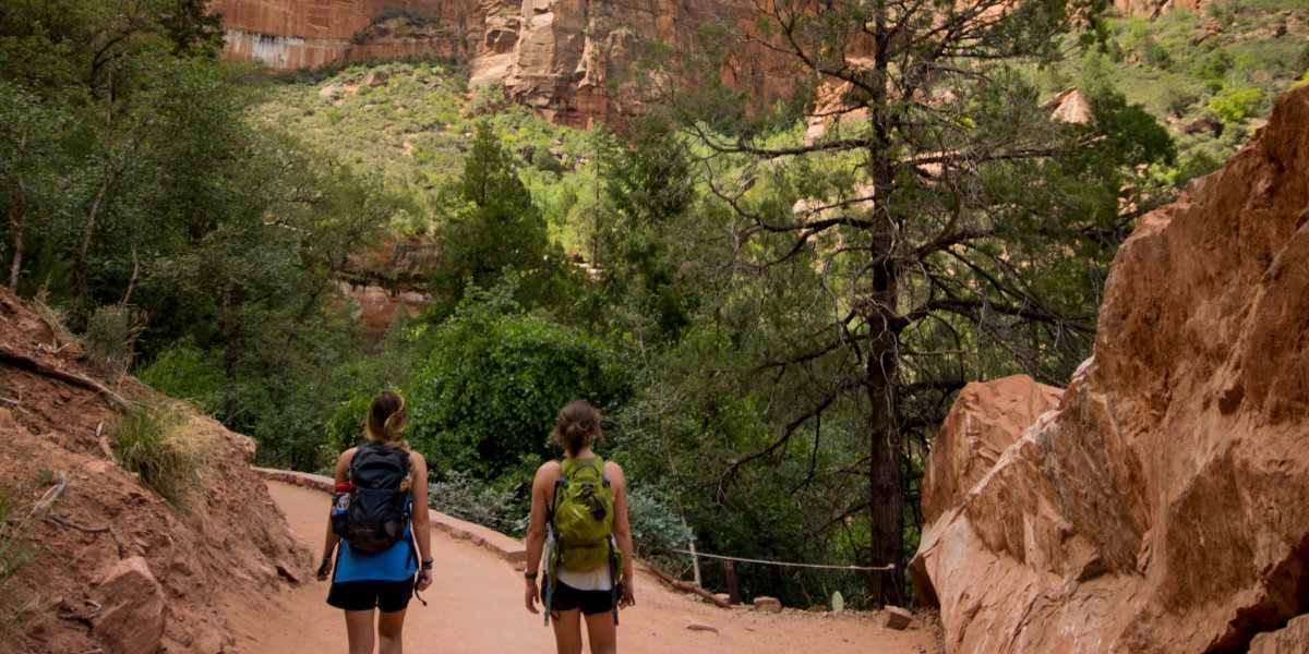 Two women hike in a national park in from of trees
