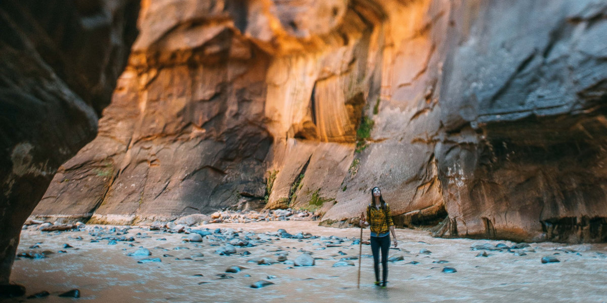 A woman hikes in a creek in a canyon