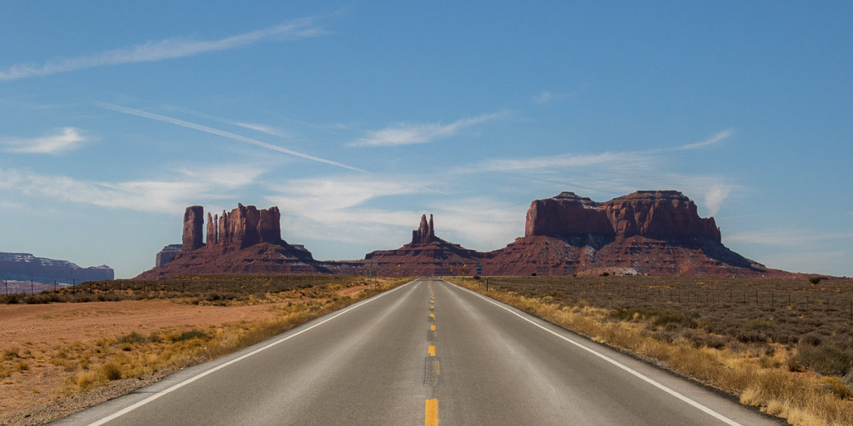 Road runs toward the monoliths of Monument Valley