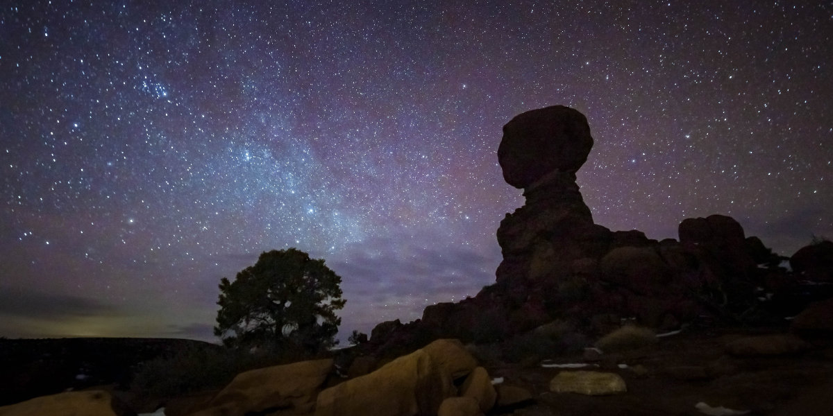 Dark night sky with sandstone formations in the front