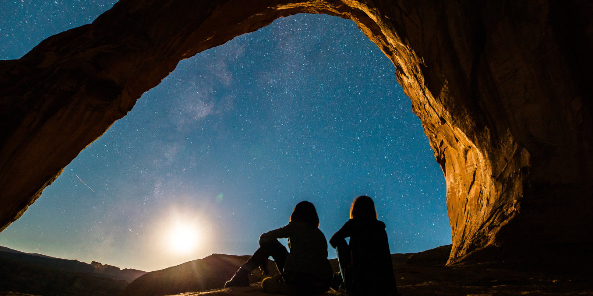Two stargazers look to the night sky as the sun sets