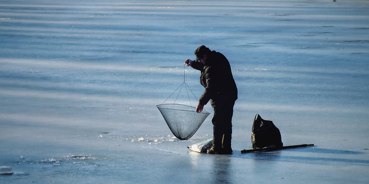 Man ice fishes on a lake