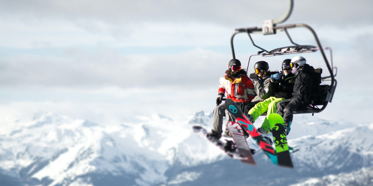 Skiers ride the lift up the mountain