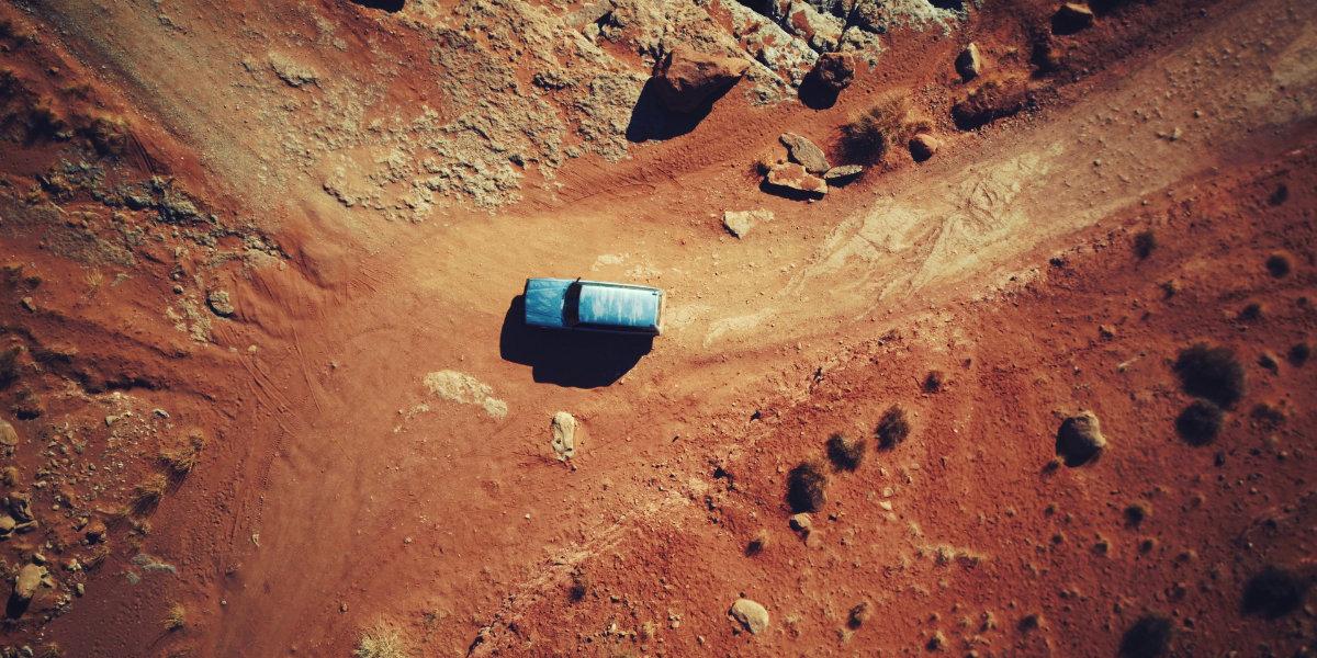 A vehicle drives across a desert floor